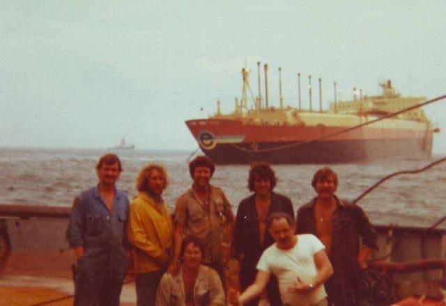 Foto de la tripulación del Tempest, al fondo el barco escorado y fondeado en la Bahia de Algeciras